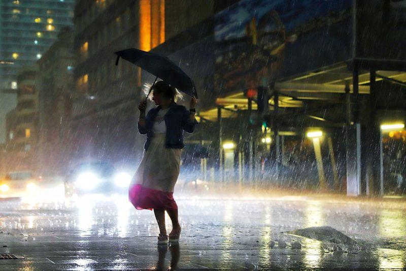 Woman under umbrella standing on street during rainfall