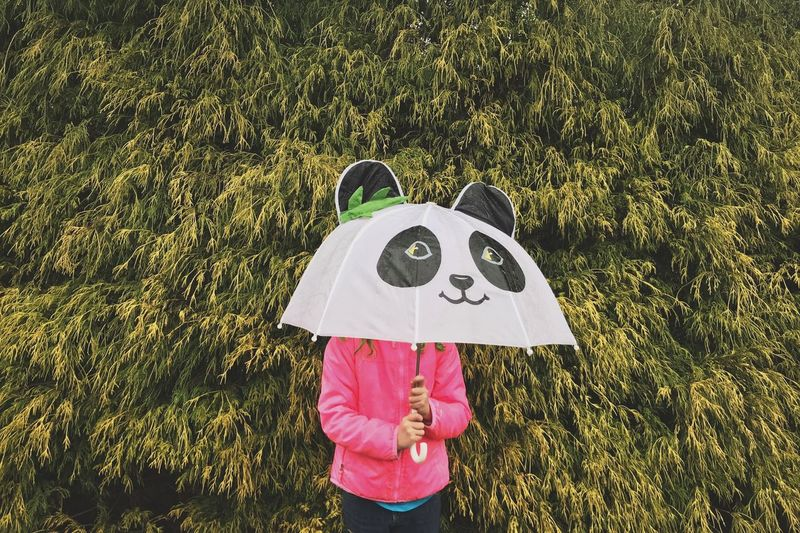 Girl holding umbrella standing against trees