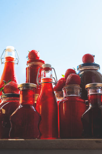 Close-up of glass bottles on table against clear sky