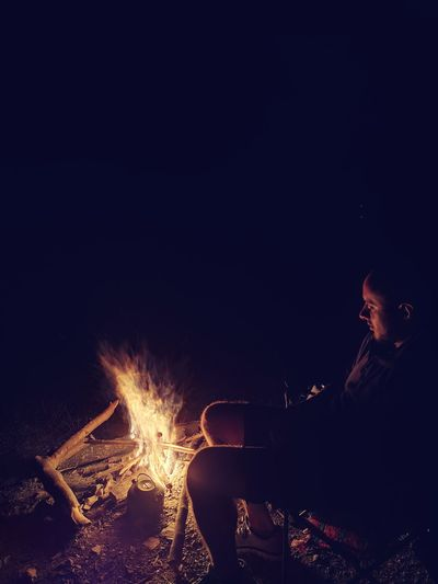 Side view of man sitting by campfire in dark at night