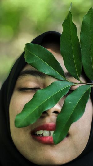 Close-up of thoughtful young woman with leaves