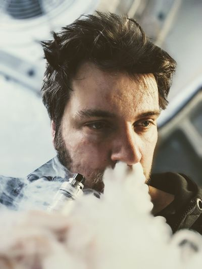 Man exhaling smoke from nose at home