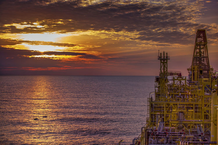 Offshore Platform In Sea Against Sky During Sunset