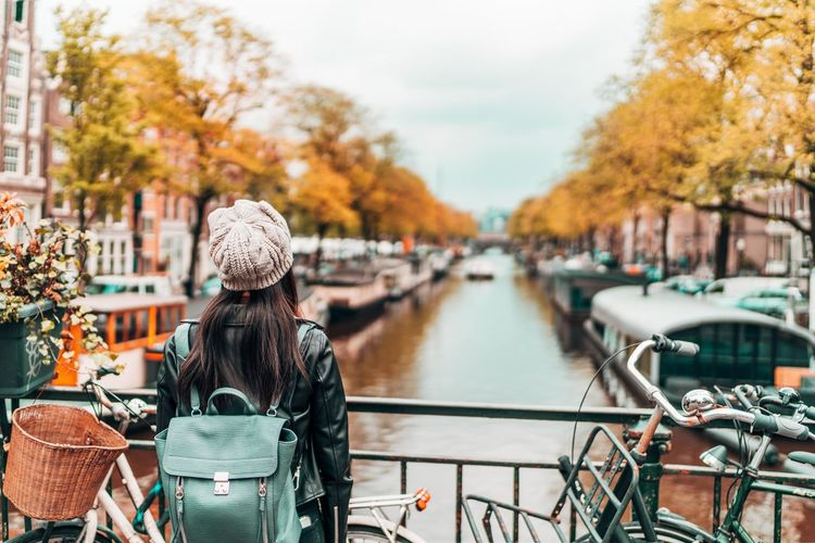 Woman standing on footbridge over canal in city