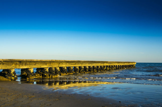 Beach Beauty In Nature Blue Clear Sky Day Horizon Over Water Landing Stage Nature No People Outdoors Pier Scenics Sea Sky Tranquil Scene Tranquility Water Wave Wooden Post