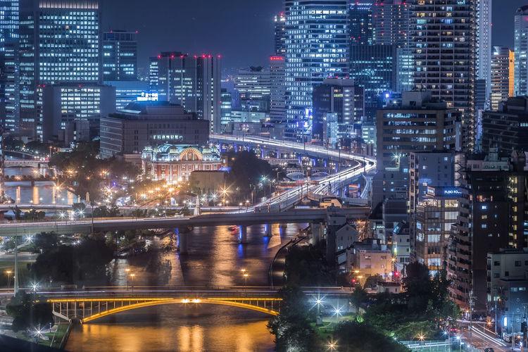 Illuminated buildings and bridge in city