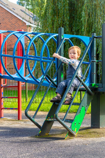 Portrait of smiling boy on slide at playground