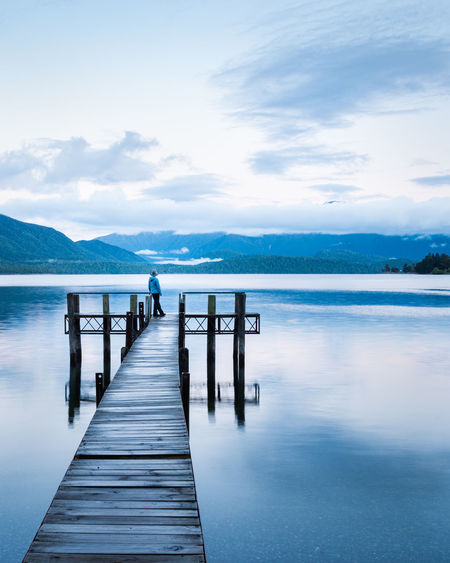 Wooden pier over lake against sky