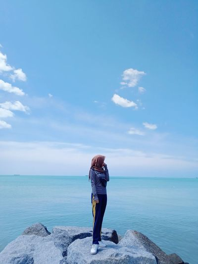 Woman looking at sea while standing on rocks against sky