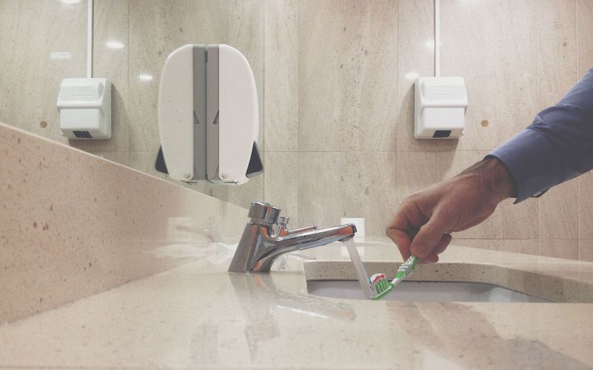 Cropped hand of man wetting toothpaste on toothbrush in bathroom
