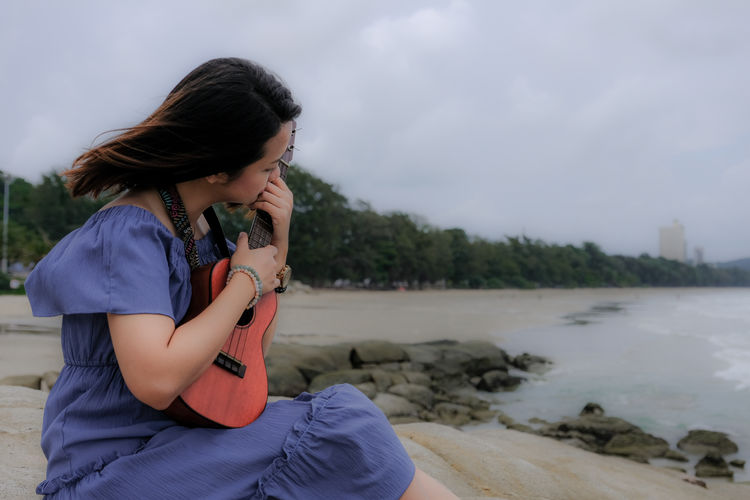 Woman playing ukulele while sitting on beach against sky