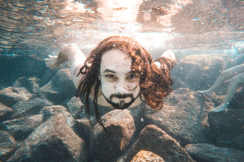 Portrait of man swimming underwater