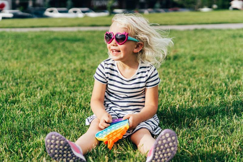 Girl wearing sunglasses sitting on field