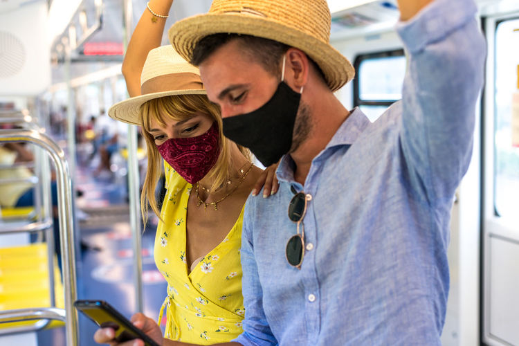 Smiling couple wearing mask using smart phone standing in bus