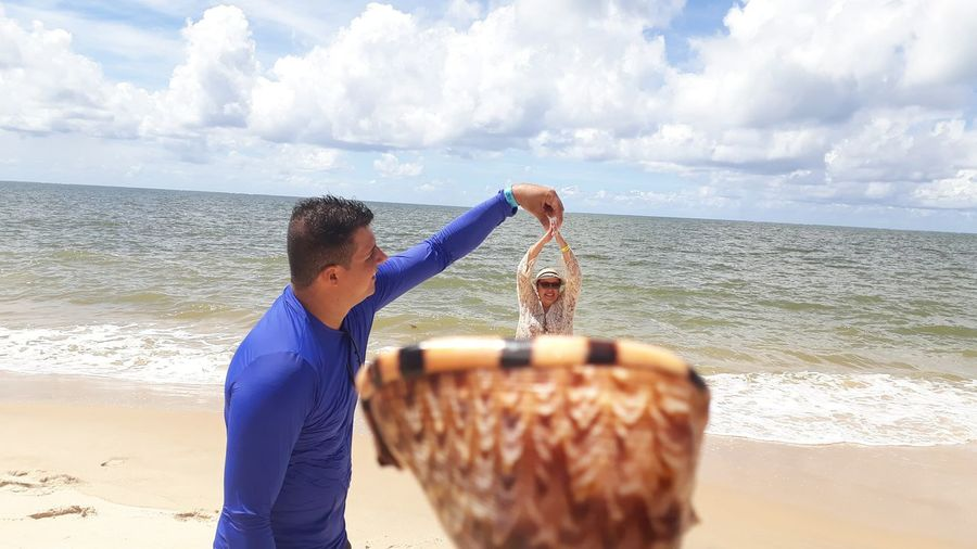 Optical illusion of man removing woman from shell at beach against sky