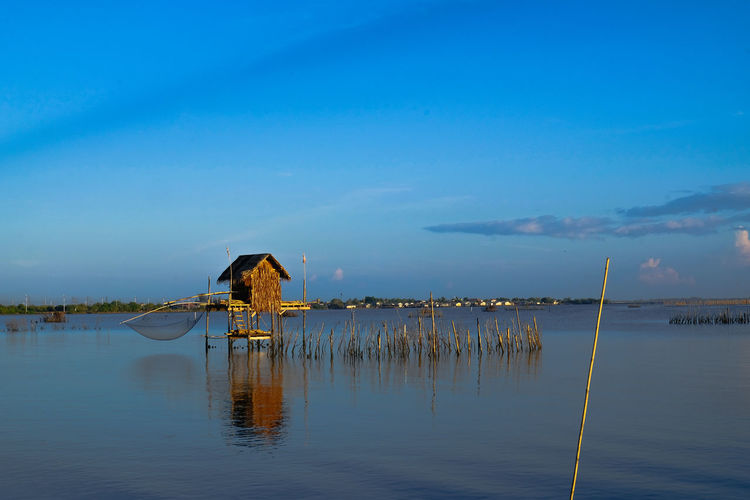 Wooden posts in lake against blue sky