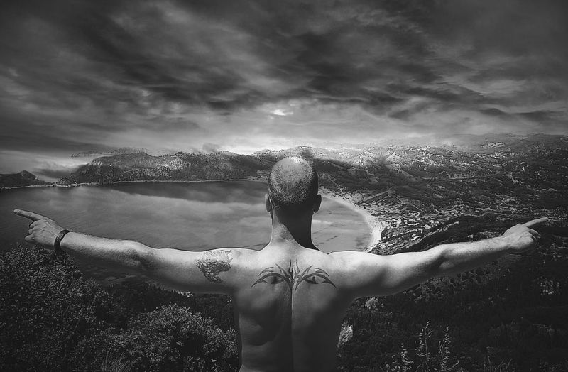 Rear view of shirtless man with arms outstretched against cloudy sky