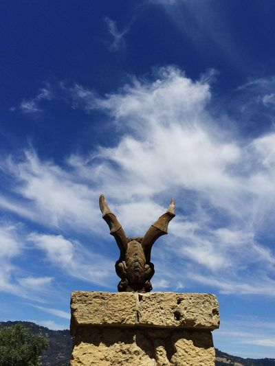 Low angle view of gargoyle sculpture against cloudy blue sky