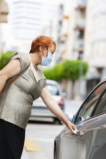Side view of woman wearing flu mask standing by car in city