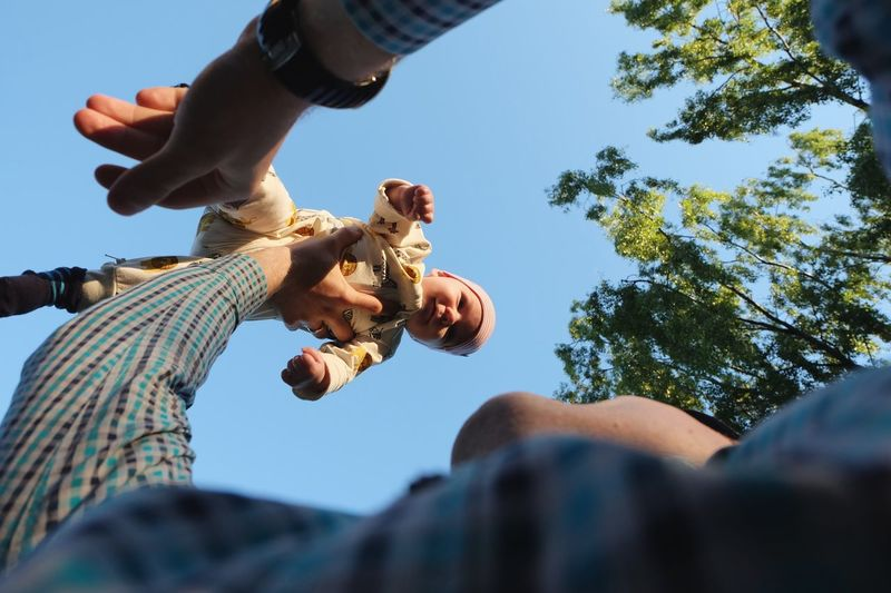 Low angle view of father lifting baby against clear sky