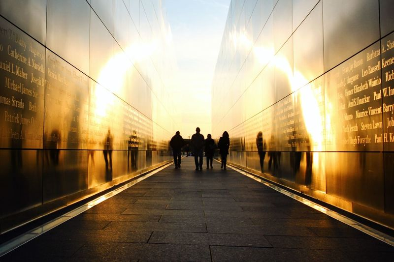 Rear view of silhouette people walking at national september 11 memorial and museum