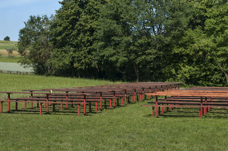 Picnic Tables And Benches On Grassy Field