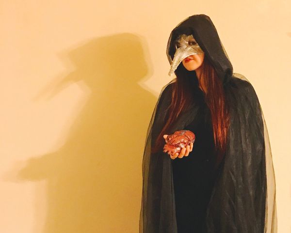 Woman Redhead Long Hair Human Organ Holding Gory Hooded Cape Black Hood Cape  Masquerade Mask Face Mask Mask Villain Darkness Heart Halloween Creepy Costume One Person Standing Lifestyles Real People Studio Shot Young Women Indoors