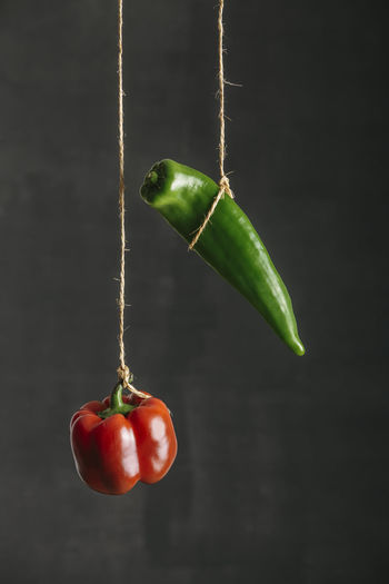 Close-up of red bell pepper hanging on plant