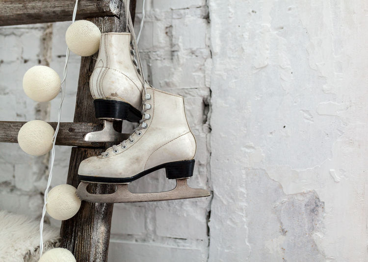 Close-Up Of Ice Skates Hanging By Ladder On Wall