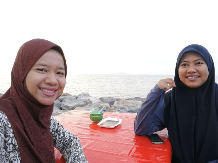 Portrait of smiling female friends in hijab sitting at table against sea
