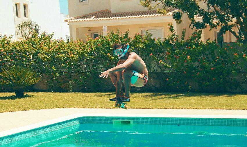 Full length of young man with skateboard jumping in swimming pool