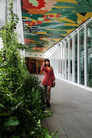 Woman standing by plants against building