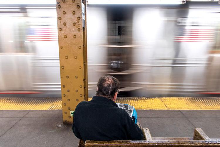 Rear view of man sitting on train at railroad station platform