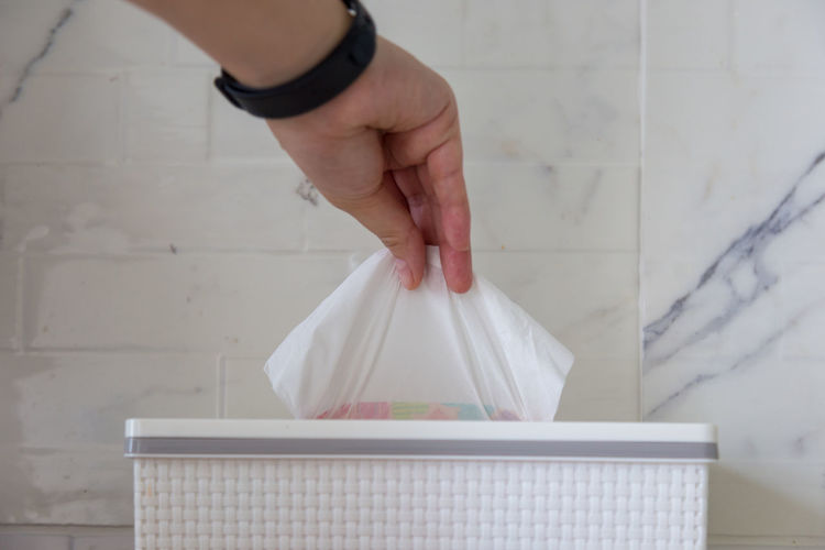 Cropped hand picking tissue paper from box against wall