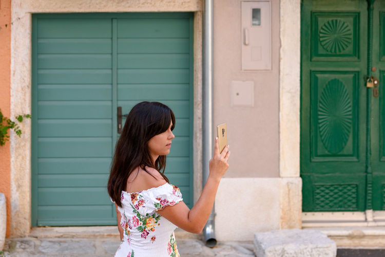 Young woman, tourist, using mobile phone, taking photos in old town.