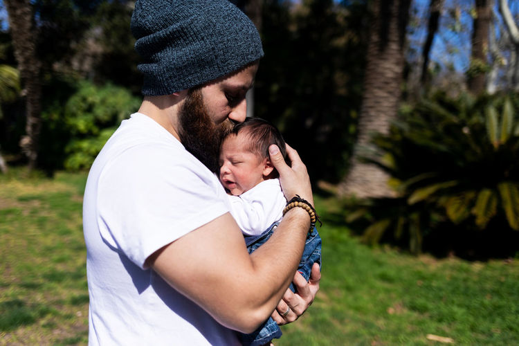 Young couple holding baby outdoors