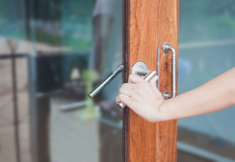 Cropped hand of person holding handle on door