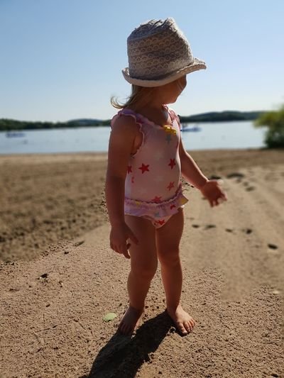 Full length of cute baby girl wearing hat standing at beach during sunny day