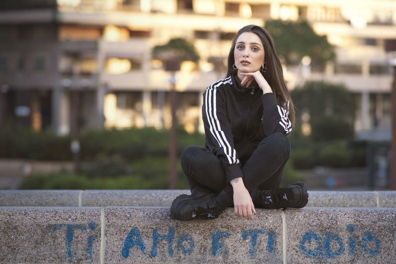 Young woman looking away while sitting on retaining wall