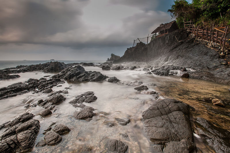 Rock Formations At Beach Against Cloudy Sky