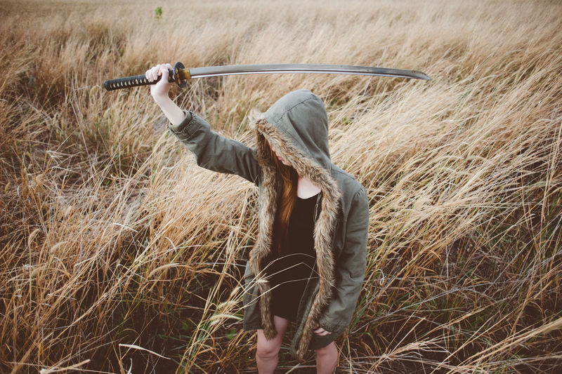 Woman holding sword while standing on field
