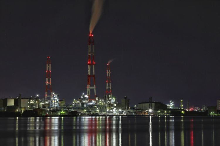 Smoke stacks in illuminated factory by lake against sky at night