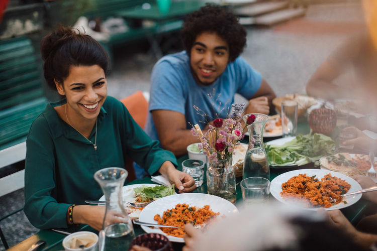 Smiling young woman looking away while enjoying dinner with male friend during garden party