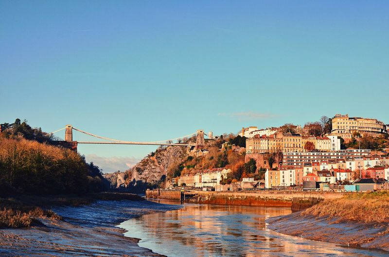 Bridge over river by buildings against clear blue sky