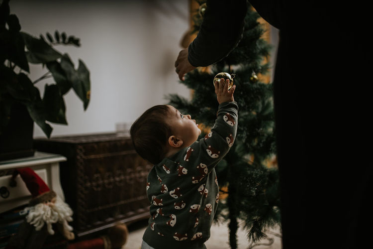 Rear view of boy holding christmas decorations