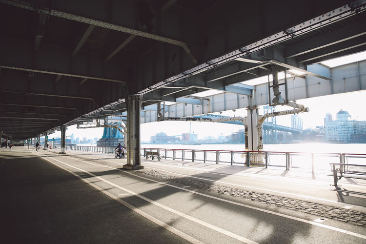 Walkway below elevated road in manhattan on sunny day