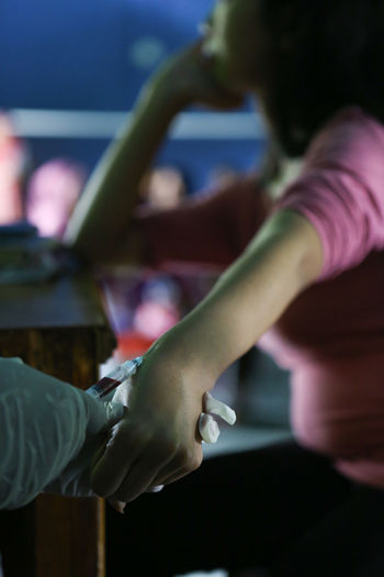 High angle view of doctor injecting syringe on woman hand