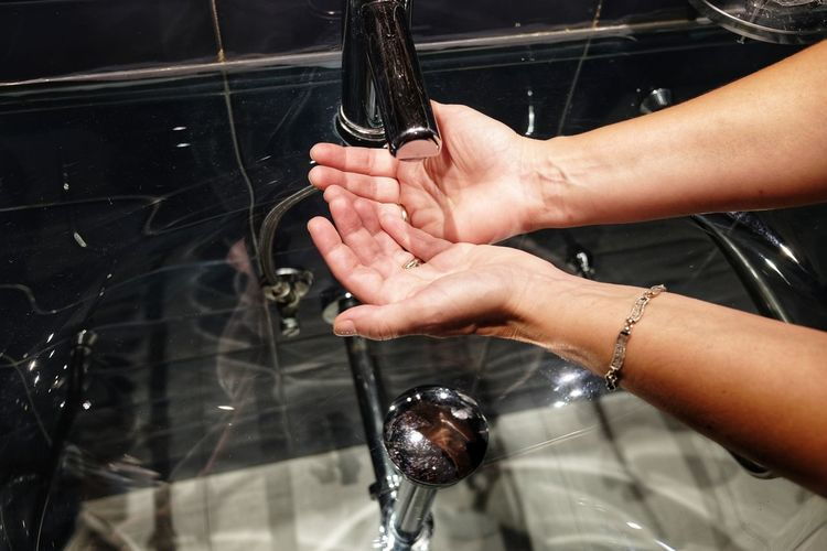 Cropped Hands Of Woman Washing Hands In Sink