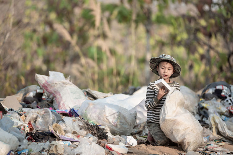 Portrait of young man sitting on garbage