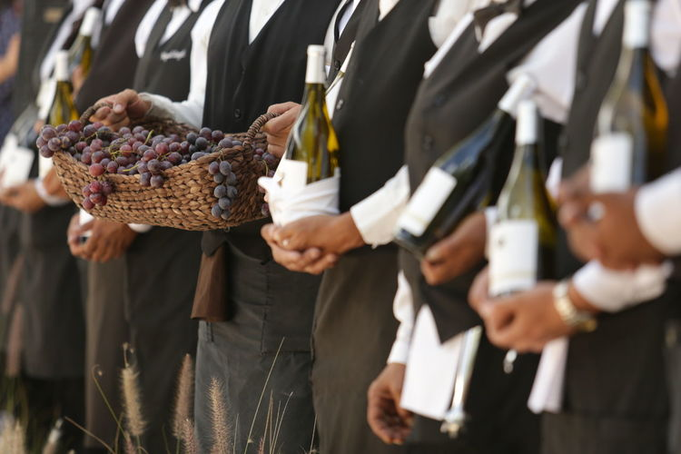 Midsection of people holding grapes and wine bottles on field